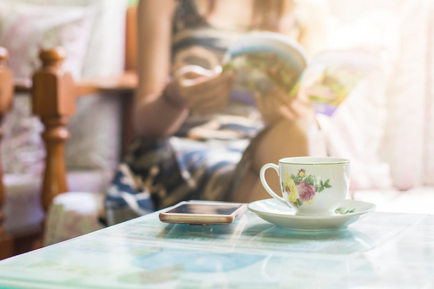 Beautiful young asian woman sitting on chair relaxing coffee time with book and smartphone at home