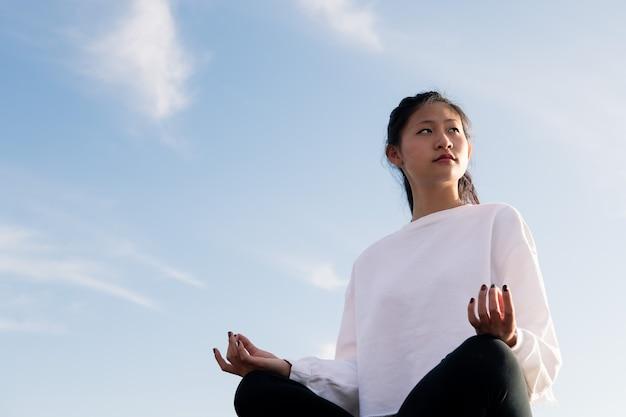 Красивая молодая азиатская женщина, сидящая, размышляя