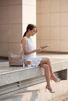 Beautiful young asian woman sitting in urban street and using tablet