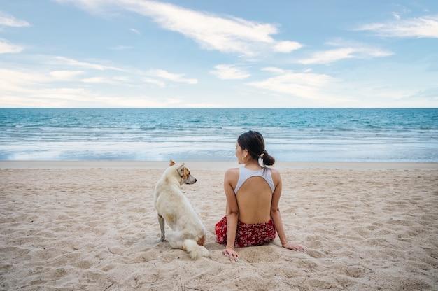 휴가 열 대 바다에서 해변에 강아지와 함께 앉아 아름 다운 젊은 아시아 여자