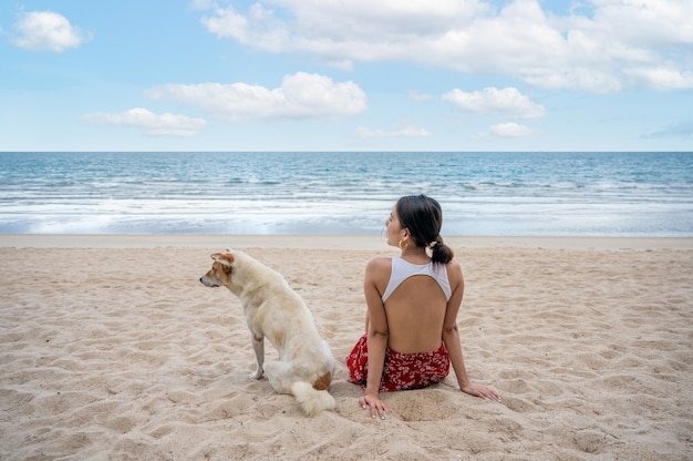 Beautiful young asian woman sitting with a dog on the beach in tropical sea on vacation. summer and holidays concept