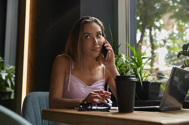 Beautiful young asian woman sitting with laptop at cafe calling by smartphone