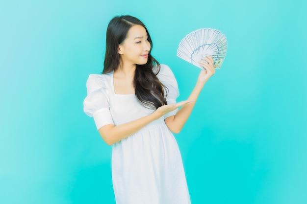 Красивая молодая азиатская женщина улыбается с большим количеством наличных денег и денег на синем