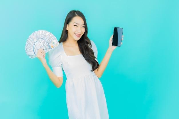 Bella giovane donna asiatica sorride con un sacco di soldi e denaro su blue