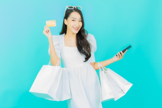 파란색에 쇼핑백을 들고 아름다운 젊은 아시아 여성 미소