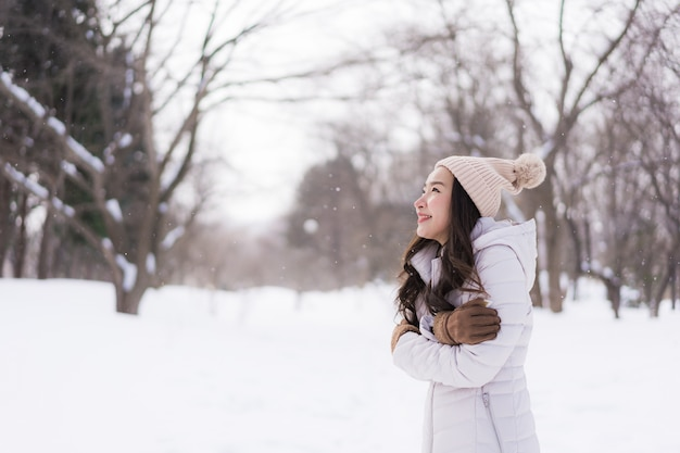 Beautiful young asian woman smiling happy for travel in snow winter season