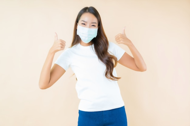 Beautiful young asian woman smiling and wearing mask for protect covid19 or coronavirus