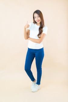 美丽的年轻亚洲女人微笑与拇指对米色