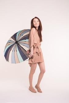 白い壁にきれいなドレスを着て縞模様の傘の下に立っている美しい若いアジアの女性。