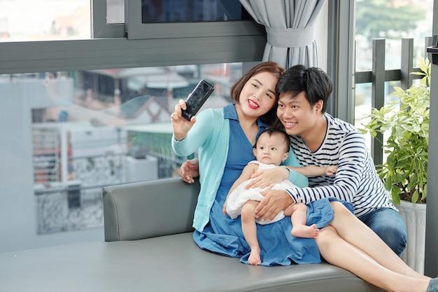 彼女の夫と小さな女の赤ちゃんとselfieを取っている美しい若いアジアの女性