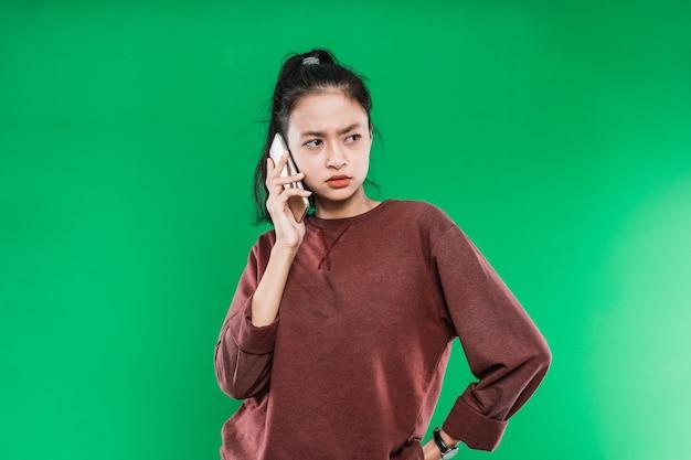 녹색 배경에 화난 표정으로 옆에 보는 동안 전화로 얘기하는 아름 다운 젊은 아시아 여자
