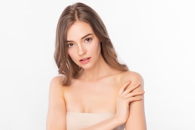 Красивая молодая азиатская женщина касаясь ее тела с свежей здоровой изолированной кожей, косметикой красоты и концепцией ухода за лицом.