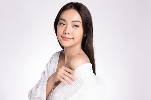 白い背景で隔離の新鮮な健康的な皮膚で彼女の体に触れる美しい若いアジア女性