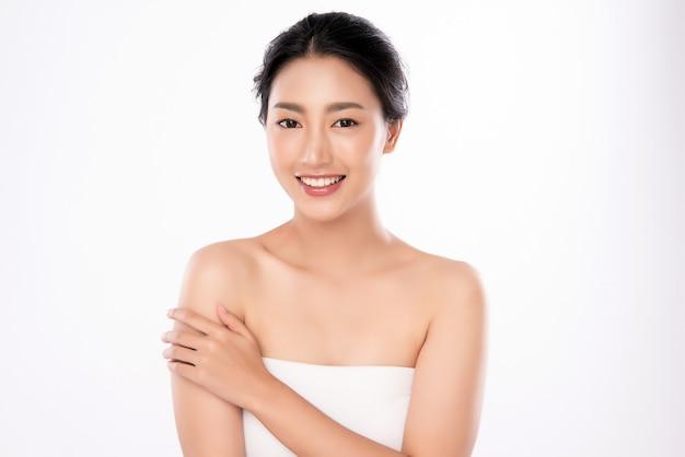 白い壁、美容化粧品、フェイシャルトリートメントのコンセプトに分離された新鮮な健康的な肌で彼女の体に触れる美しい若いアジア女性