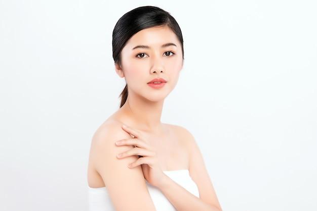 白い壁、美容化粧品、フェイシャルトリートメントのコンセプトに分離された新鮮な健康な皮膚で彼女の体に触れる美しい若いアジア女性。