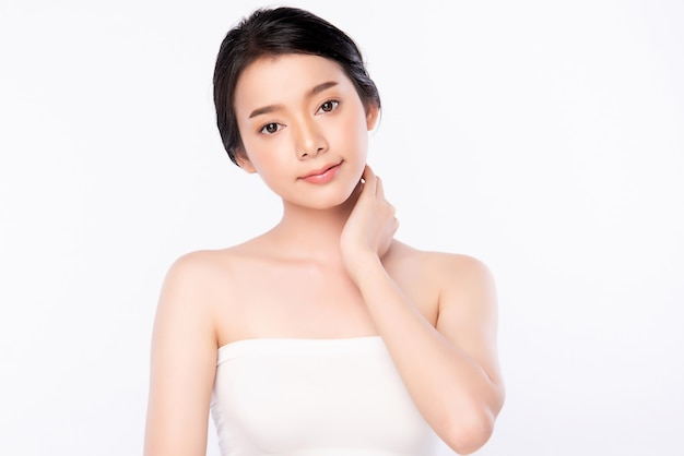 白で隔離され、新鮮な健康的な皮膚と彼女の体に触れる美しい若いアジア女性