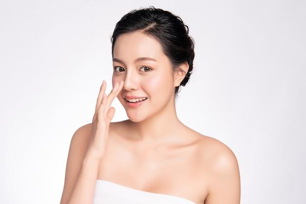 Красивая молодая азиатская женщина касаясь ее чистому лицу с свежей здоровой изолированной кожей, косметикой красоты и концепцией ухода за лицом