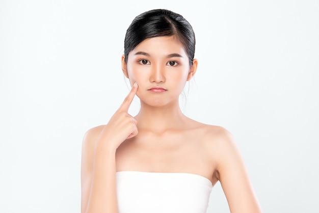 新鮮な健康な皮膚、分離、美容化粧品、フェイシャルトリートメントのコンセプトで彼女のきれいな顔に触れる美しい若いアジア女性