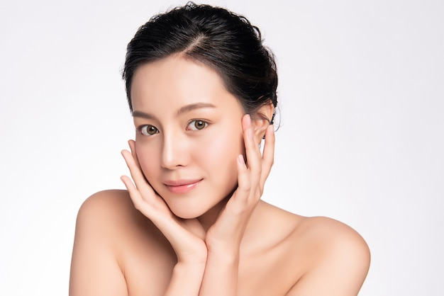 Beautiful young asian woman touching her clean face with fresh healthy skin, isolated, beauty cosmetics and facial treatment concept