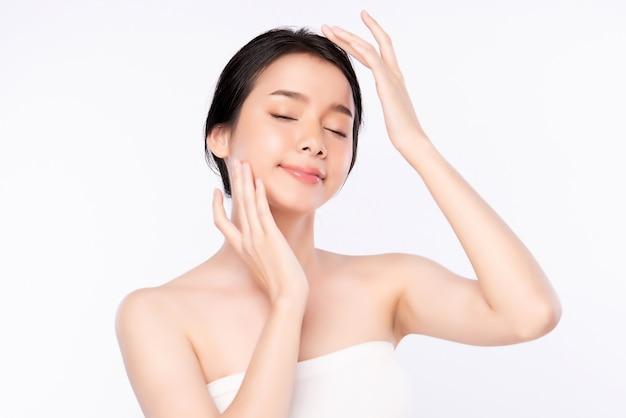 白で隔離され、新鮮な健康的な皮膚で彼女のきれいな顔に触れる美しい若いアジア女性