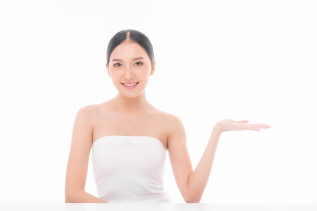 Beautiful young asian woman touching her face with clean skin , fresh skin , and posing her empty hands with blank space for advertising - facial treatment , cosmetology , beauty and spa concept