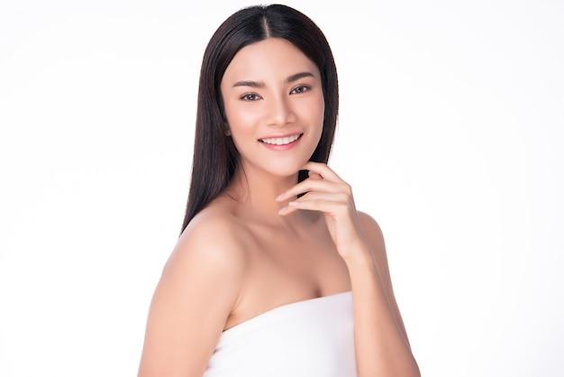 清潔で新鮮な肌と柔らかい頬と笑顔に触れる美しい若いアジア女性。幸福と陽気で、白で隔離、美容と化粧品、
