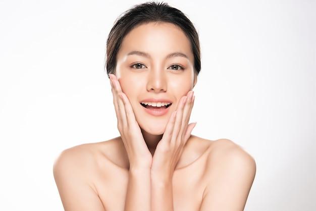아름 다운 젊은 아시아 여자 부드러운 뺨을 만지고 깨끗하고 신선한 피부와 미소. 행복과 쾌활한, 흰색, 미용 및 화장품,