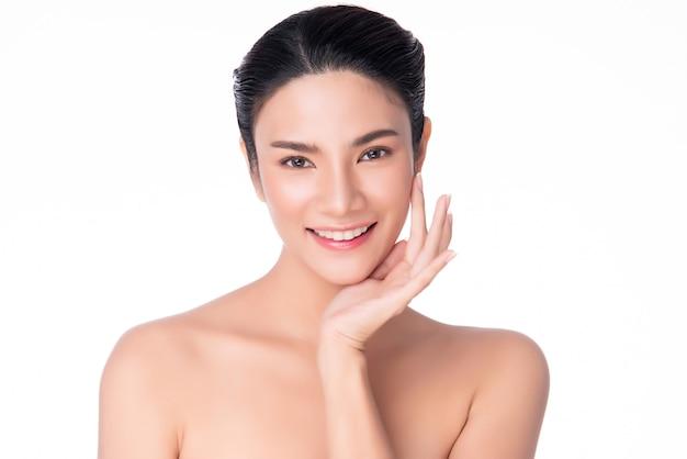 깨끗하고 신선한 피부와 부드러운 뺨을 만지고 미소 아름 다운 젊은 아시아 여자
