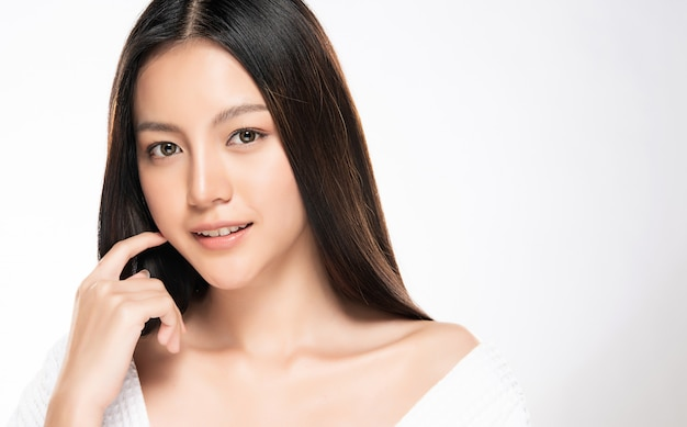 Beautiful young asian woman touching soft cheek and smile with clean and fresh skin. happiness and cheerful with, isolated on white wall