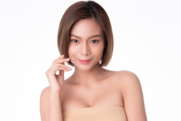 Beautiful young asian woman touching soft cheek and smile with clean and fresh skin