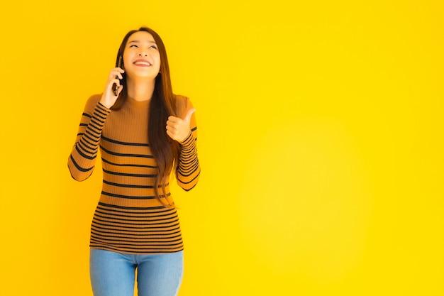 美しい若いアジア女性は黄色の壁に多くのアクションを持つスマートな携帯電話や携帯電話を使用します。