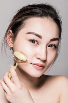 完璧な肌にヒスイのフェイスローラーを使用して美しい若いアジア女性。美容顔のクローズアップ。半貴石を使ったフェイシャルトリートメントのコンセプト。コピースペースと灰色に分離