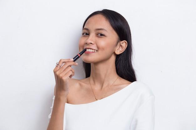 흰색 배경에 고립 된 립스틱을 사용하는 아름다운 젊은 아시아 여성