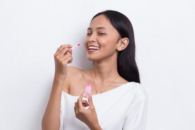 白い背景で隔離の口紅を使用して美しい若いアジアの女性