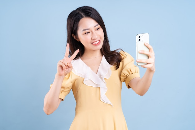 Beautiful young asian woman using smartphone on blue background