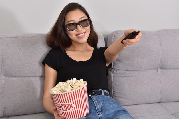 Красивая молодая азиатская женщина смотрит телевизор дома. есть попкорн. время дома