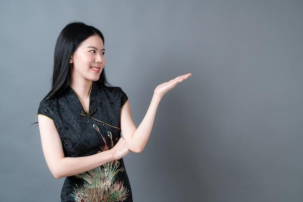 美しい若いアジアの女性は、手で提示する黒の中国の伝統的なドレスを着ています