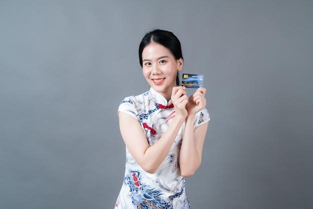 아름 다운 젊은 아시아 여자 회색 표면에 신용 카드를 들고 손으로 중국 전통 복장을 착용
