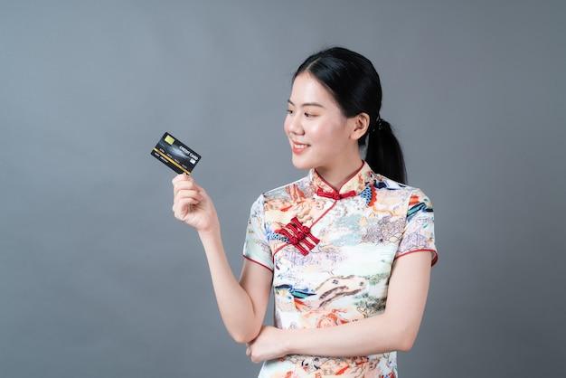 美しい若いアジアの女性は灰色の表面にクレジットカードを持っている手で中国の伝統的な衣装を着ています