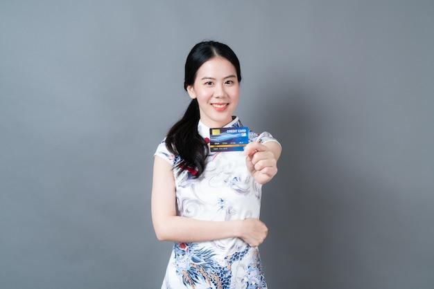 아름 다운 젊은 아시아 여자 회색 벽에 신용 카드를 들고 손으로 중국 전통 복장을 착용