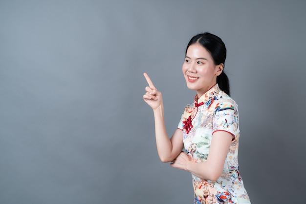 美しい若いアジアの女性は灰色の表面で側面に提示する手で中国の伝統的なドレスを着ています