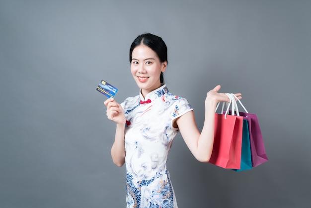 美しい若いアジアの女性は灰色の背景にショッピングバッグとクレジットカードで中国の伝統的な衣装を着ています