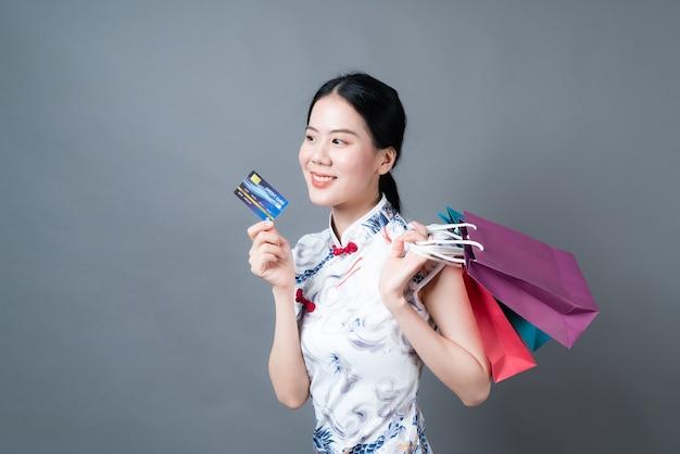 아름 다운 젊은 아시아 여자 회색 표면에 쇼핑 가방과 신용 카드로 중국 전통 드레스를 착용