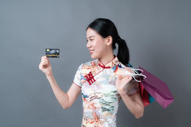 美しい若いアジアの女性は灰色の表面に買い物袋とクレジットカードで中国の伝統的な衣装を着ています