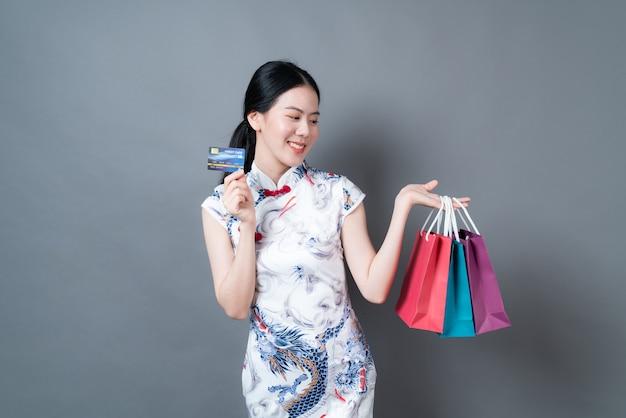 아름 다운 젊은 아시아 여자 회색 벽에 쇼핑백과 신용 카드로 중국 전통 드레스를 입으십시오