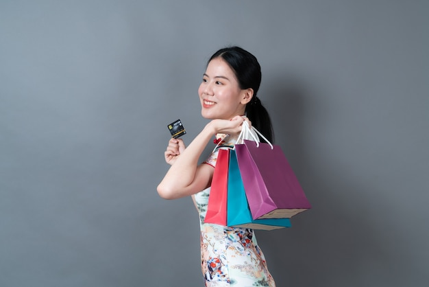 美しい若いアジアの女性は灰色の壁に買い物袋とクレジットカードで中国の伝統的な衣装を着ています