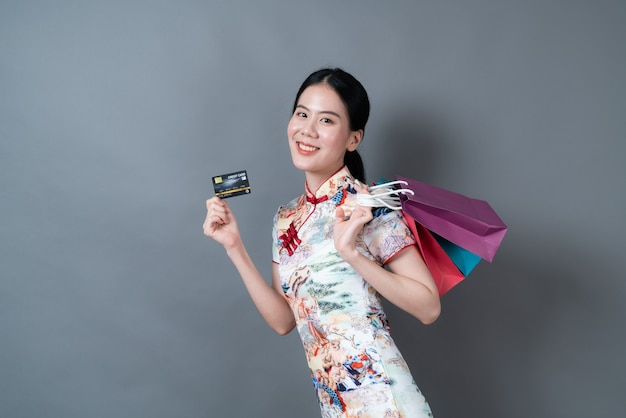 Beautiful young asian woman wear chinese traditional dress with shopping bag and credit card on grey background