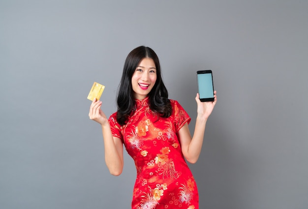 Красивая молодая азиатская женщина носит красное китайское платье, используя смартфон и держа кредитную карту