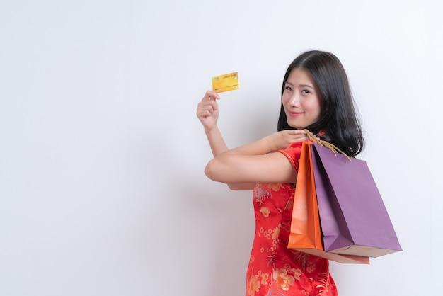 Красивая молодая азиатская женщина носит красное китайское традиционное платье, держа кредитную карту и хозяйственные сумки