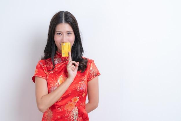 Красивая молодая азиатская женщина носит красное китайское традиционное платье, держа кредитную карту с белым и копировальным пространством